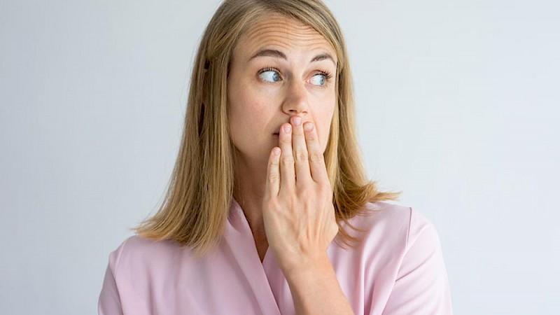 Frau mit Mundgeruch und Hand vor dem Mund.