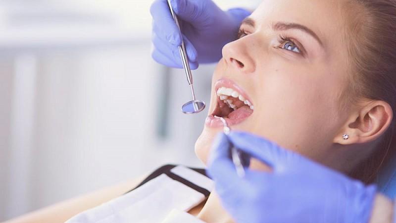 Frau lässt sich aufgrund Mundgeruch bei einem Arzt untersuchen.
