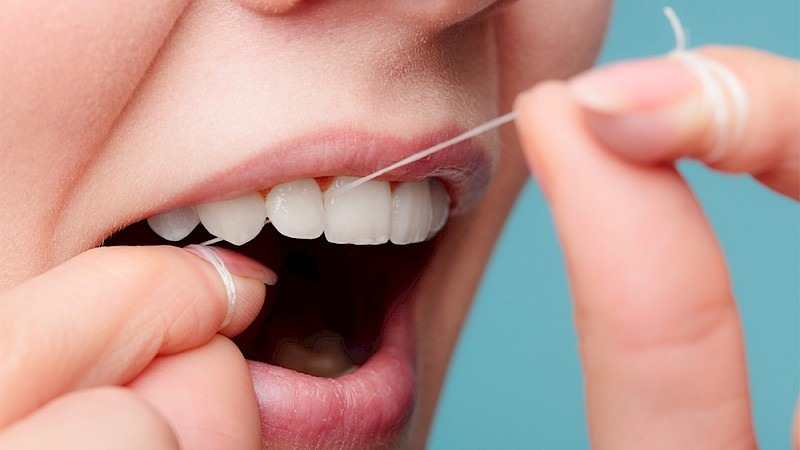 Zahnstein mit Zahnseide vorbeugen.